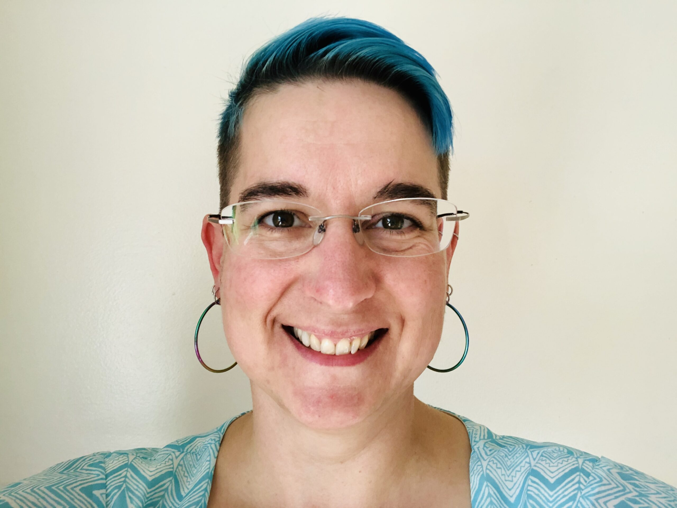 Photo of a woman with short blue hair and large hoop earrings.